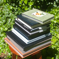 Stack of albums from a 9x6 skinny flush up to a 13x13 hybrid matted-flush (a la carte albums)